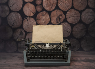 Vintage typewriter with a clean yellowed old sheet of paper. on a background of a tree of rustic logs. for the design of your text design