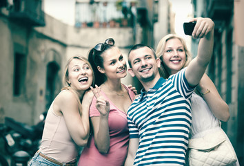 Four cheerful smiling friends taking self portrait