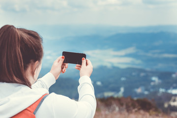 Young bruntte woman taking picture from view point of slovak tatras, landscape photo