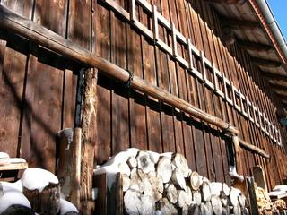 Verschneite Stapel mit Brennholz vor einer alten Scheune im Winter mit Sonnenschein in Rudersau bei Rottenbuch in Oberbayern