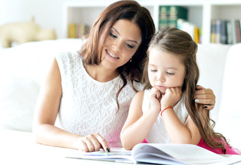 little cute girl reading book with mother