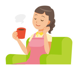 A female home helper wearing an apron sits on the sofa and is drinking coffee