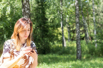 Young redhead woman using the phone outdoors on a sunny day.  Portrait redhead woman on the phone with copy space