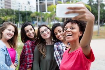 African american woman taking selfie with group of international girlfriends