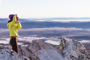 Young woman photographs in the mountains. Portrait of a photographer taking a photos with dslr camera, covering her face with the camera.  Photographer taking travel nature photography. Text space.