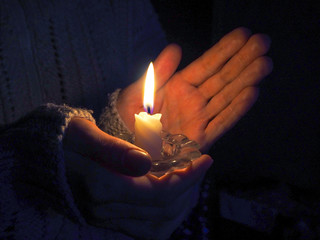 Burning candle in female hands at night.