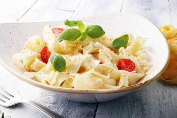 fettucine pasta white cream sauce with tomato and basil in white plate - Italian food style