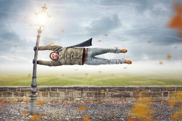 Mann im Sturm hängt an einer Laterne