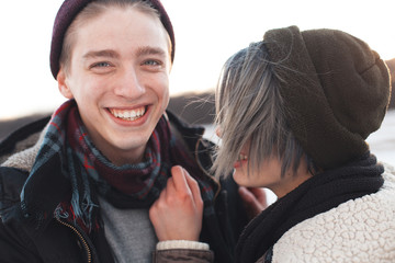 A happy young woman and man walking outdoors at winter. Close up