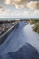 Residue of furious strong stormy waves near a concrete dam coastline in France