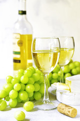 Two glasses of white wine,cheese and grapes .
