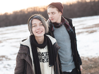 Girl and young man walking outdoors. Winter
