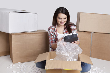 Smiling young woman sitting on the floor with lots of cardboard boxes. Happy female open box found gift holds a in his hands