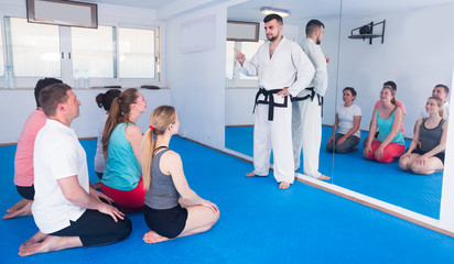 Karate instructor is showing new martial moves to adults