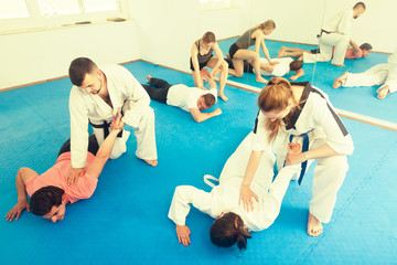 trainees sparring in pairs to practice new holds in taekwondo cl
