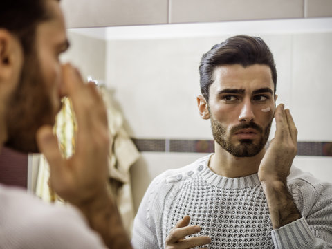 Handsome young man applying moisturizing cream on face in front of home bathroom mirror