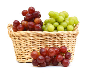 Fresh red and green grapes in basket Isolated on white