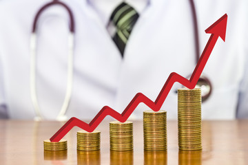 Red arrow over stack of money coins arranged as a graph on wood table with blurry the doctor stethoscope around neck a scene in the back, concept of financial health and medical expenses