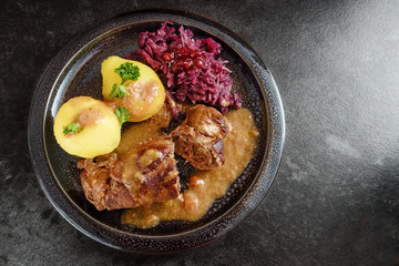 beef rolls, traditional german meal, filled meat rouladen with red cabbage, potatoes and sauce on a dark plate, dgray slate stone background with copy space