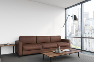 White living room, brown sofa, poster
