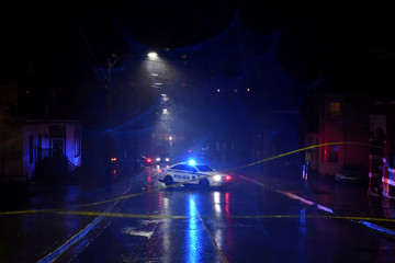 A police car blocks the scene of a downed power line as heavy rain and gusting winds from Winter Storm Grayson cause disruptions in Halifax