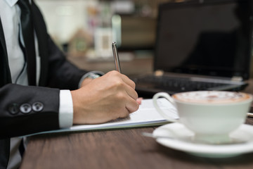 Close up businessman is signing a contract, business contract details at coffee shop