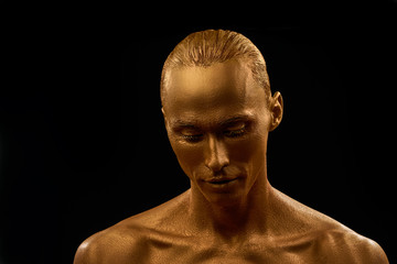 man in gold paint portrait. guy looks down with eyelids lowered almost closed eyes on black background