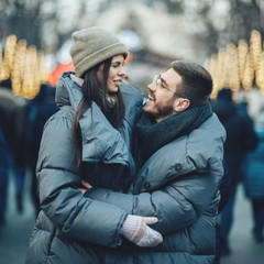 Christmas romantic sensual couple in love to cold winter day over celebration city bokeh, gentle kiss moment
