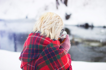 Girl drinking hot tea in the winter forest, close up, horizontal format