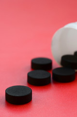 Several black tablets fall out of the plastic jar on the red surface. Background image on medical and pharmaceutical topics. Activated Charcoal