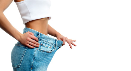 Woman in oversize jeans after weight loss.