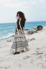stylish young fashionable woman walking on the beach