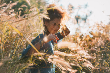 cheerful young woman on a field at sunset
