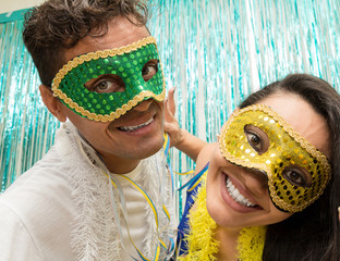 Couple uses Carnaval masks in Brazil, they look at the camera..