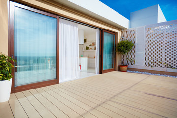 roof top patio with open space kitchen, sliding doors and decking on upper floor