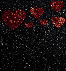 Faded red Valentine's day hearts on a black glittery background with white dots