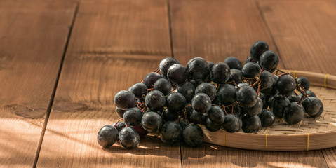 The seedless black grapes on a wooden table Fototapete