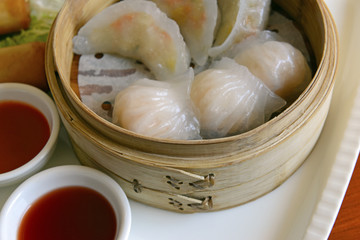 Dim Sum, Dumplings and Chinese buns on plate in bamboo basket