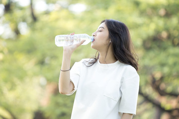 Attractive Asian Woman drinking water at garden. Woman with health care concept.