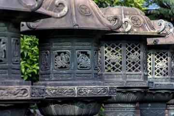 Stone lanterns in Ueno Park, Taito ward, Tokyo, Japan. Line of japanese traditional lanterns or light towers at Ueno Toshogu Shrine.