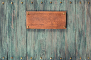 Signboard blank on vintage old mint green wooden wall planks texture background. Retro style filtered photo