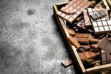 Broken chocolate bars on wooden tray.