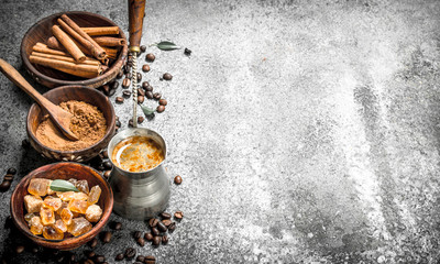 Coffee background. Coffee in turkey with crystals of sugar, cinnamon and ground coffee.