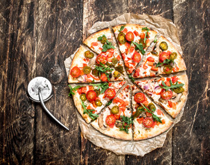 fresh pizza with tomatoes and greens.