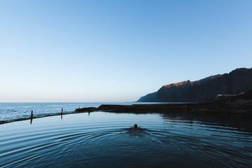 Man swimming in calm water in natural pool near ocean at dawn