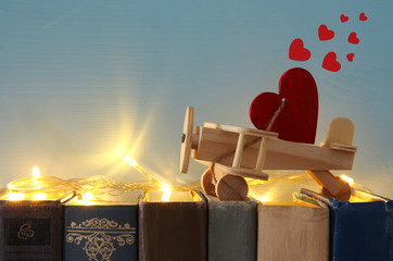 Valentine's day background. Wooden toy plane with heart over old books.