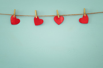 Valentine's day background. hearts hanging in front of wooden background.