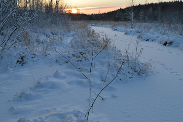 Sunrise over the frozen snowy winter forest river