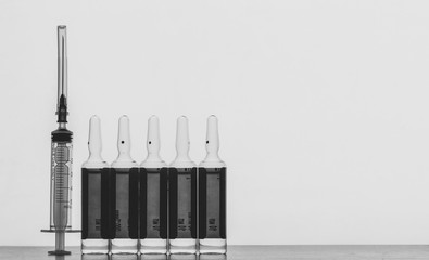 a disposable syringe and ampoules with a solution for injection on a grey background with space for text, black and white photo