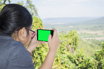 Beautiful women are taking pictures of the natural scenery with her mobile phone. When traveling on holiday